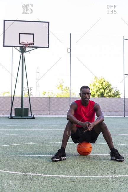 Calm African American sportsman sitting on basketball on playground looking away