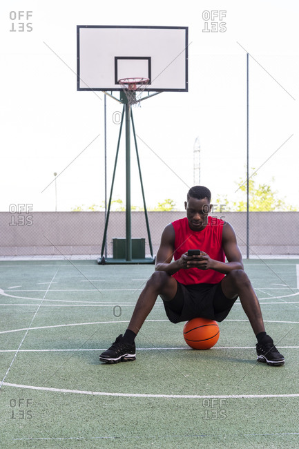 Calm African American sportsman sitting on basketball on playground and texting on mobile phone while looking away