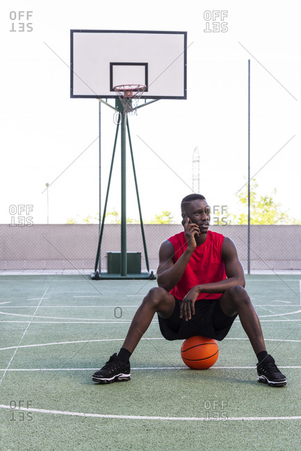 Calm African American sportsman sitting on basketball on playground and speaking on mobile phone while looking away