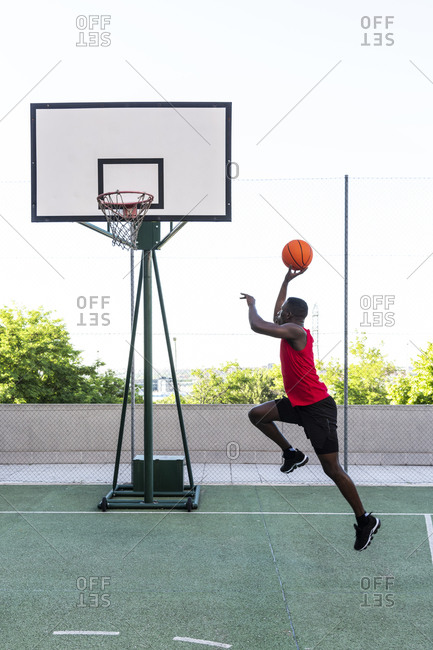 Side view of African American sportsman jumping above ground while playing basketball during training and throwing ball into hoop