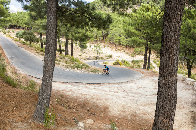 mature woman training road bike, climbing a mountain road, panoramic view