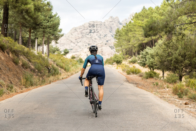 mature woman training road bike, climbing a mountain road, back view