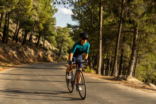 mature woman training road bike, climbing a mountain road, front view