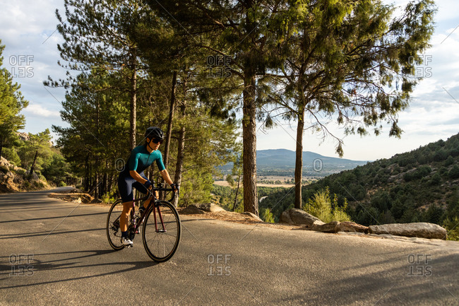 mature woman training road bike, climbing a mountain road, side view panoramic, resting sit on the bike