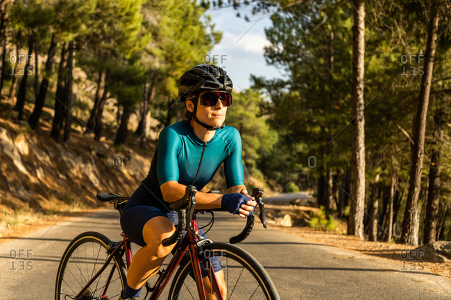 mature woman training road bike, climbing a mountain road, resting sit on the bike