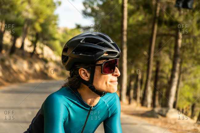 mature woman training road bike, climbing a mountain road, closed up side view
