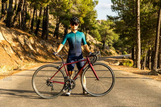 mature woman training road bike, climbing a mountain road, showing the bike on the road
