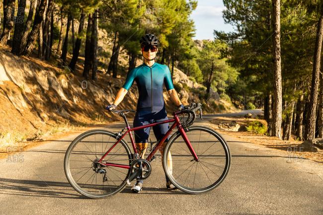 mature woman training road bike, climbing a mountain road, showing the bike on the road
