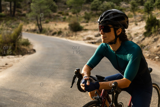 mature woman training road bike, climbing a mountain road, resting sit on the bike, side view