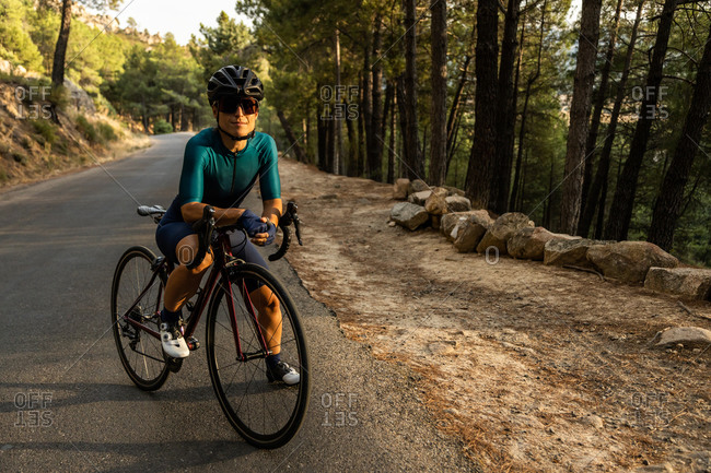 mature woman training road bike, climbing a mountain road, resting sit on the bike, front view