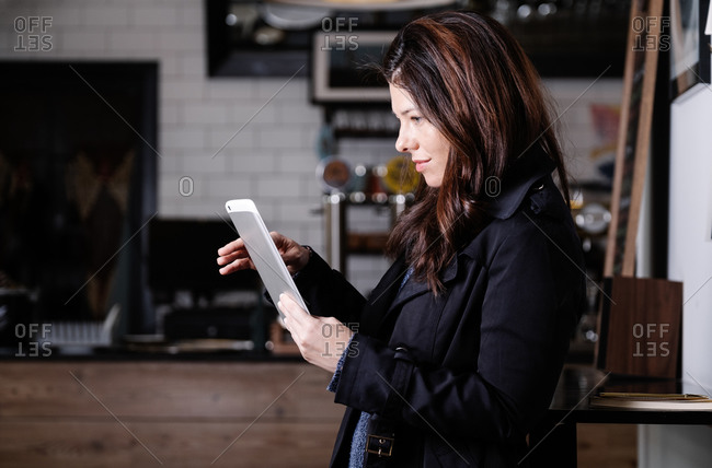 Side view of pensive female freelancer standing in cafe and using tablet while working on startup project