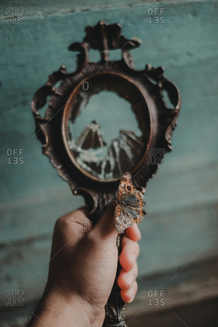 Crop anonymous person with butterfly on hand holding vintage mirror reflecting rocky mountains