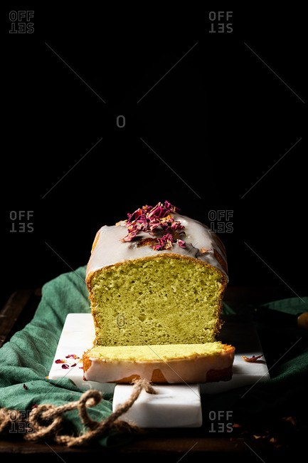Tasty homemade cake with glaze and flower petals served on plate on table in studio on black background