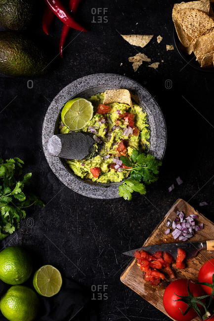 From above of vegetarian guacamole with tomatoes and lime garnished with fresh parsley and placed on black table