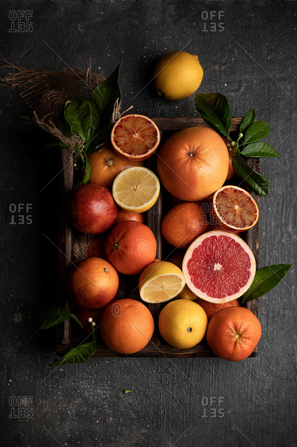 Top view of various ripe citrus fruits and green leaves on wooden tray placed on table