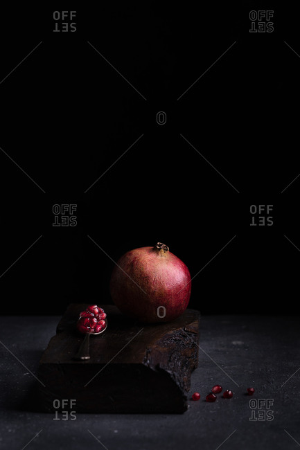 Fresh whole pomegranate and seeds in spoon arranged on wooden board in dark studio on black background