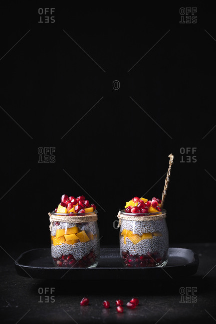 Glass jars with various tropical fruits placed on tray on table on black background in studio