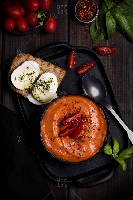 From above of delicious thick tomato soup placed on tray with toast and fresh basil on wooden table