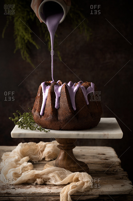 Crop anonymous cook pouring blueberry glaze on tasty chocolate Bundt cake placed on table in dark cozy kitchen