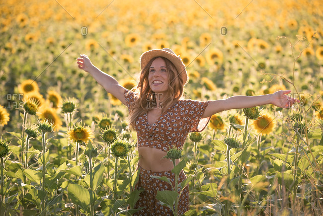Optimistic young female in summer outfit and hat standing looking away with outstretched arms amidst blooming sunflowers in field and enjoying sunny day