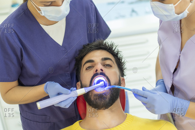 Female assistant holding suction device while dentist using mirror and drill on teeth of bearded man in clinic
