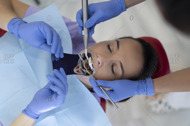 Dentist using mirror and drill on teeth of African American lady in clinic