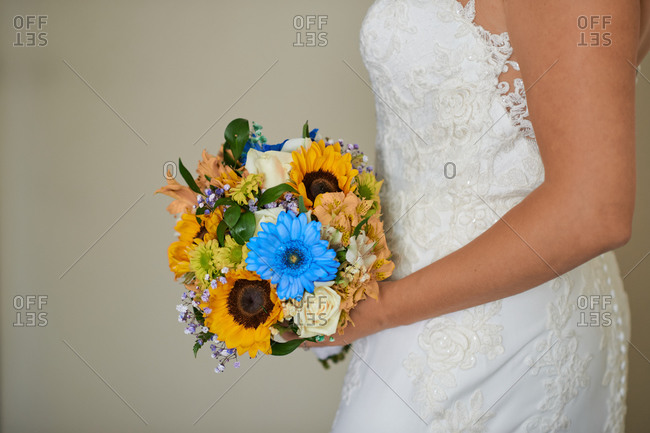 Side view of unrecognizable bride in elegant white dress standing with bouquet of delicate flowers at home on wedding day