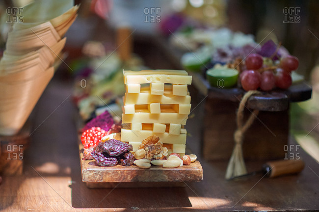 Assorted tasty appetizers placed on wooden table served for party celebration on sunny day