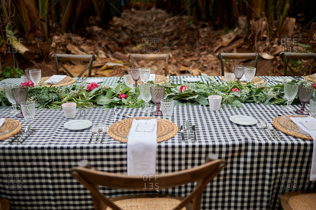 Served table and chairs placed in exotic garden with tall banana trees for celebration of event in summer