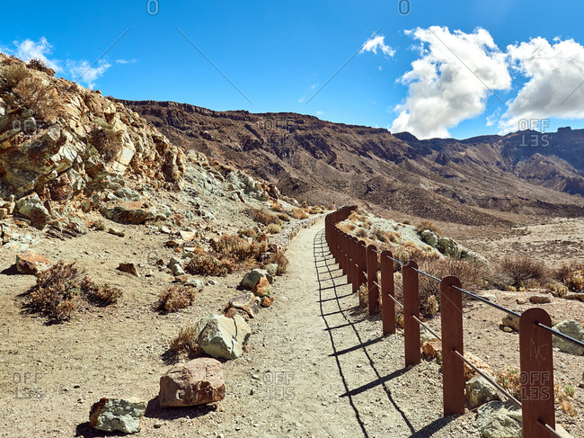Old wooden fence going along sandy walkway in highland area on sunny day on background of Mount Teide