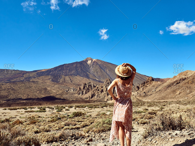 Back view of female tourist in summer dress standing in valley admiring Mount Teide located in Tenerife during vacation