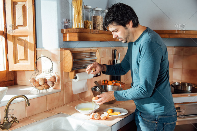 Side view of adult male separating egg yolks and whites while making dough for pastry in home kitchen