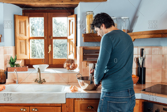 Back view of male cook mixing ingredients for dough with wooden spatula while preparing traditional Catalan waffles neula in home kitchen