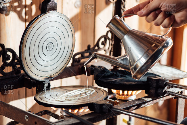 Crop anonymous person pouring liquid dough from metal kettle on waffle iron placed on gas stove while preparing typical Catalan neula biscuits in kitchen