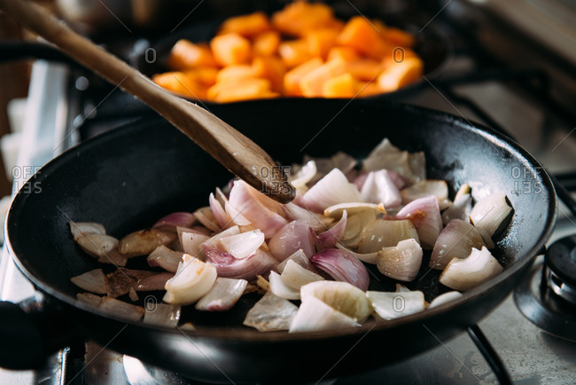 Closeup of frying pan with chopped red onion on stove during preparation of vegetarian cream soup