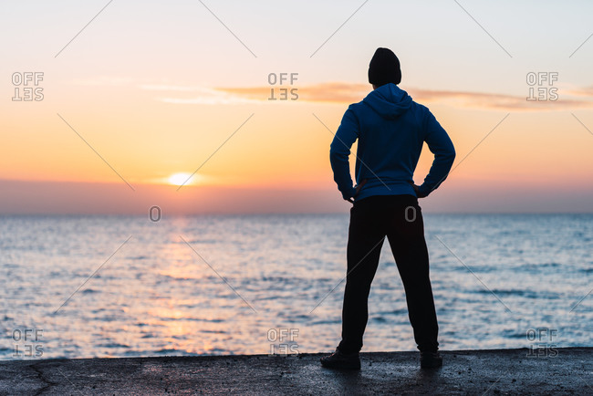 Full body back view of unrecognizable active male in warm sportswear standing on embankment near sea and admiring sunset while resting after outdoor training