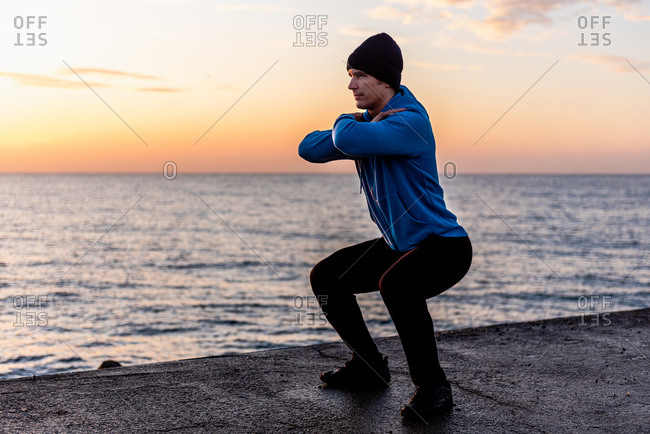 Full length of focused sportive ethnic male in activewear doing squats while warming up before training on seafront