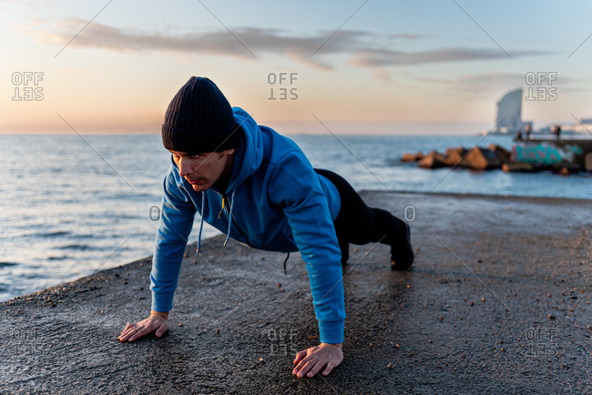 Full length of focused adult ethnic male in warm sportswear doing push ups exercise on concrete embankment near sea at sunset time