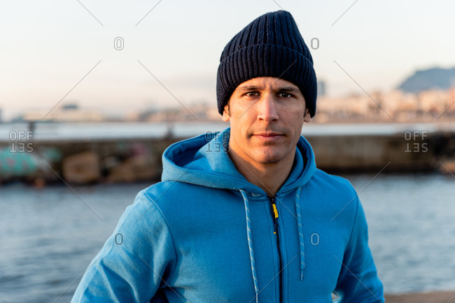 Confident adult ethnic male in warm sportive hoodie and knitted hat looking at camera while standing on embankment near sea at sunset time
