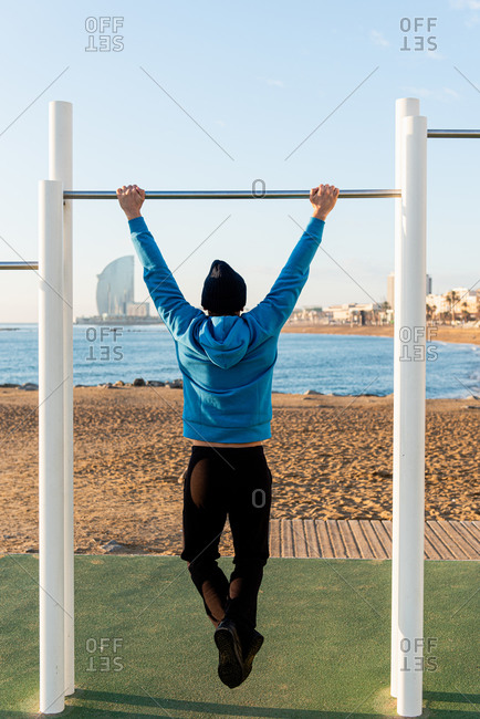 Full body back view of athletic male in warm activewear doing pull ups on metal bar while exercising on sports ground on urban beach