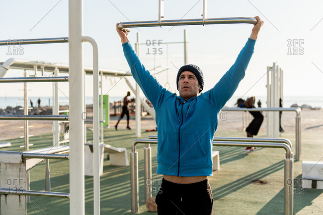 Active ethnic male in warm sportswear hanging on pull ups bar while training on sports ground with fitness equipment