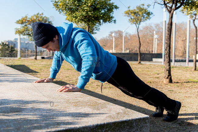 Full body side view of adult sportsman in warm activewear doing push ups exercise against concrete bench during outdoor fitness training in city