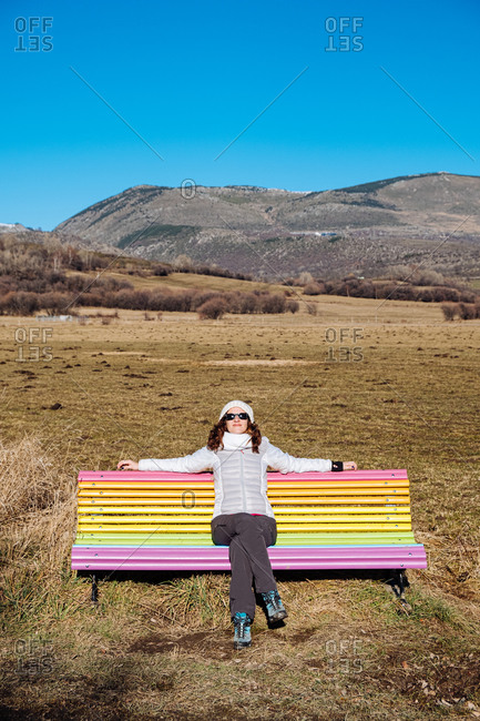 Full length of relaxed female traveler in warm wear sitting alone on colorful bench on grassy terrain against mountains in sunny spring day with blue sky