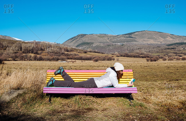 Full body side view of female traveler in warm activewear lying on colorful bench and reading book on grassy terrain with mountains and blue sky in background