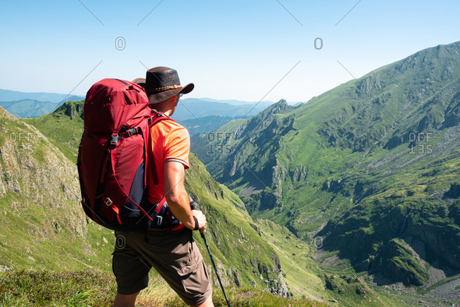 Back view of unrecognizable male hiker with backpack and trekking stick standing on grassy hilltop and admiring spectacular scenery of mountain ridge in summer day