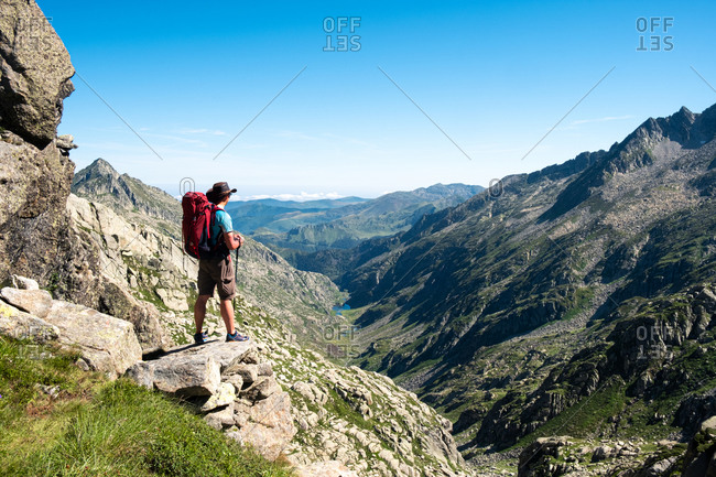 Back view of unrecognizable male hiker with backpack and trekking stick standing on rocky hilltop and admiring spectacular scenery of mountain ridge in summer day
