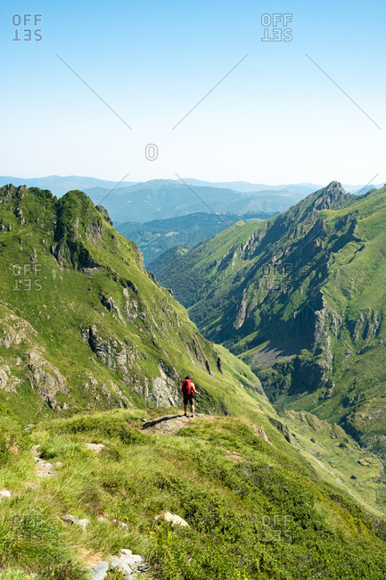 Back view of distant unrecognizable male hiker with backpack and trekking stick standing on grassy hilltop and admiring spectacular scenery of mountain ridge in summer day