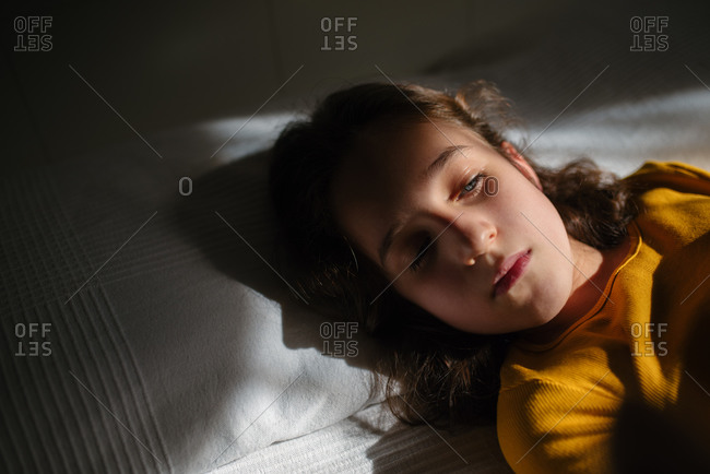 Close up view of preteen girl with wavy dark hair looking down while lying on bed during free time at home