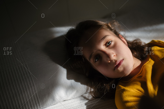 Close up view of preteen girl with wavy dark hair looking at camera while lying on bed during free time at home