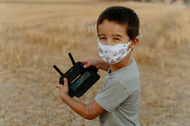 Side view of little Asian boy in protective mask looking at camera using remote control while playing with flying drone in field